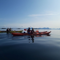 Team-paddling-Norway-coast-on-background